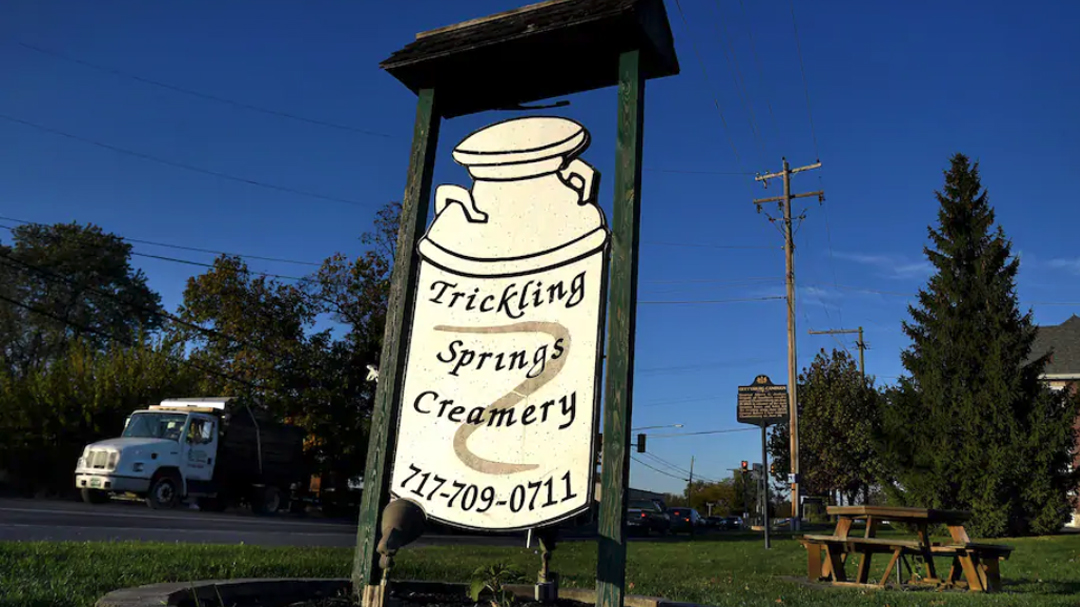 Old Trickling Springs Creamery sign in front of picnic table